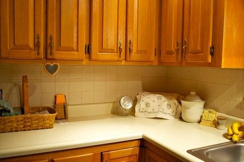 Сочетание кремового фартука с деревянными фасадми кухни