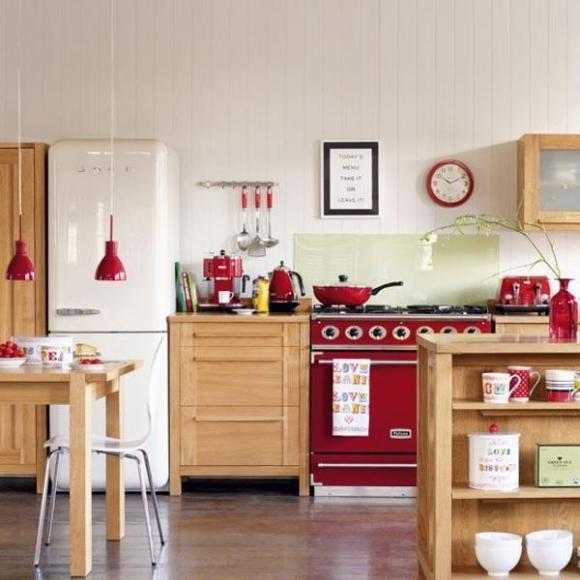 Красный цвет техники и посуды удачно подчеркивает ретро-стиль кухни из светлого дерева.